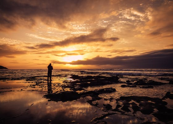 A man fishes at sunset in Bluff, South Africa.