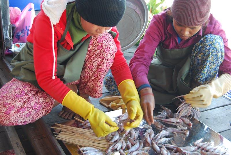 Two women process fish