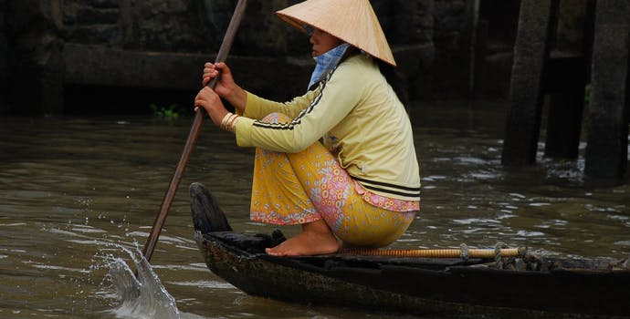 Woman rows to a floating market.