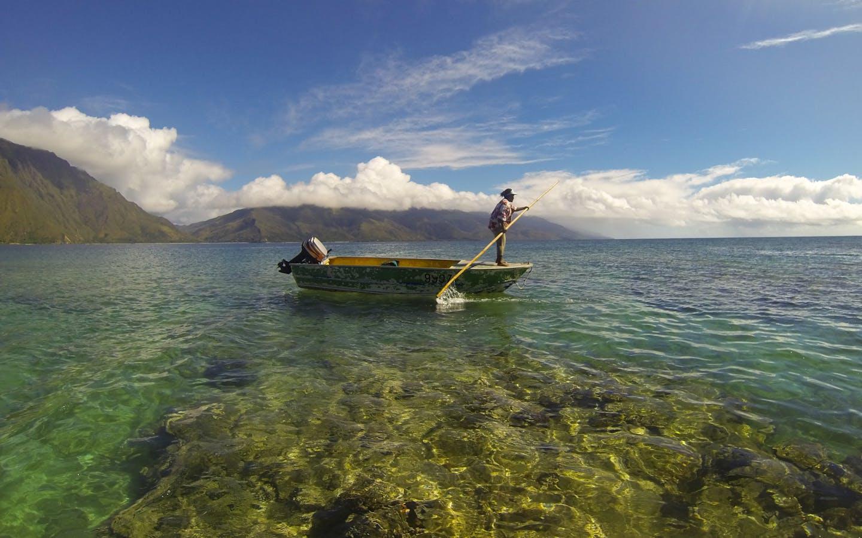 A fisherman paddles his boat.