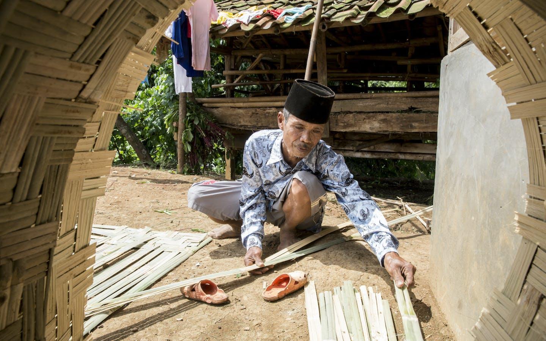 Pak Ahmud, age 60, constructing bamboo siding