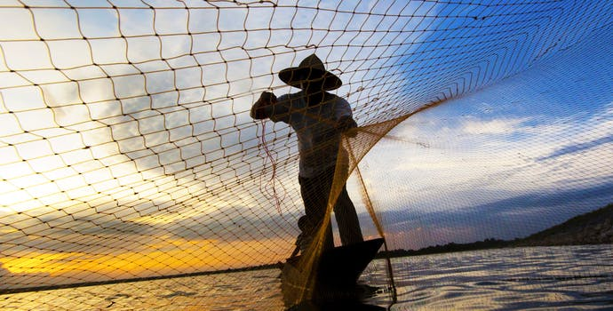 Man and boy fishing at sunset in Thailand.