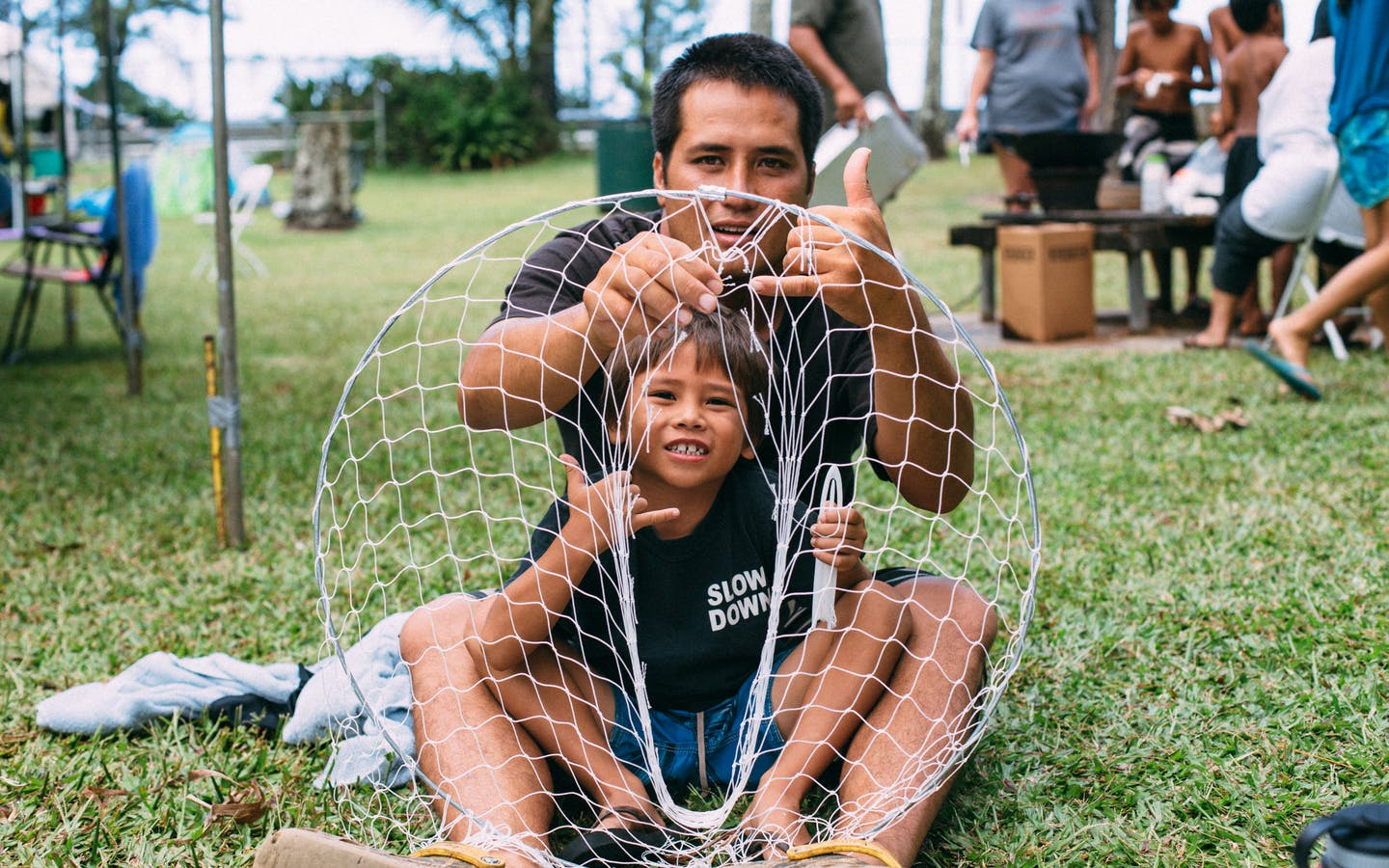 young boy and his father holding the net, Hawaii.