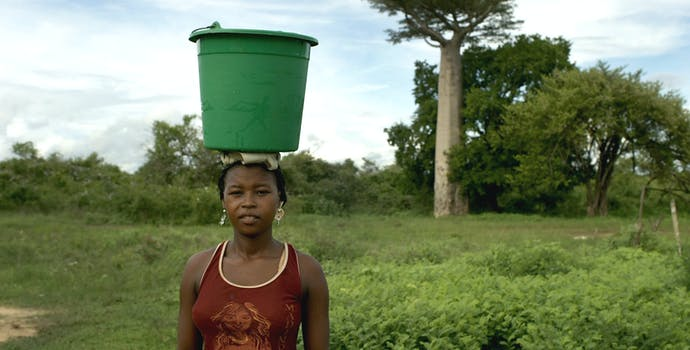 A local woman with a bucket of water.
