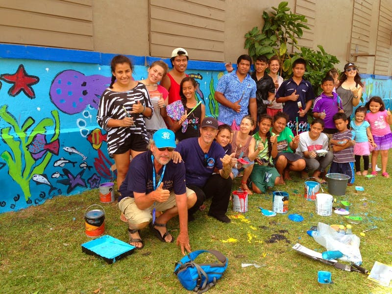 Greg Stone and ocean artist Wyland (bottom left) finish up painting a mural with a group of kids in Samoa.