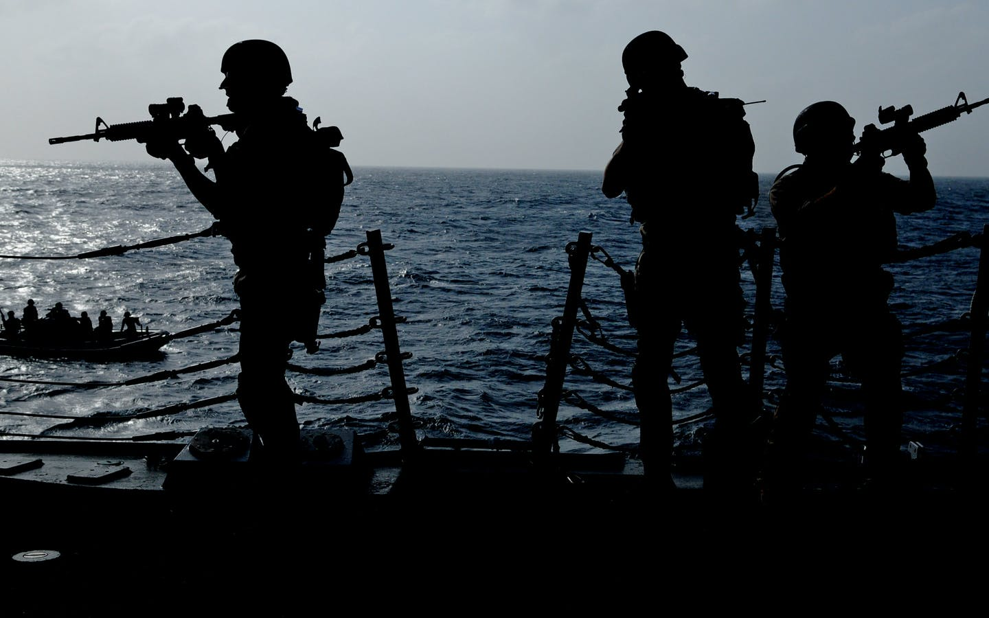 Silhouette of soldiers on a ship with a smaller ship in the background