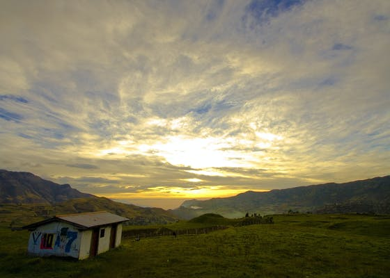 Sunset over mountains, fields, and building in Cuenca, Ecuador.