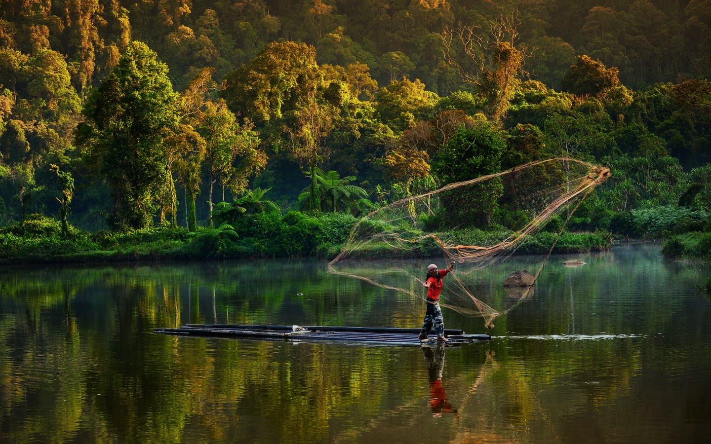 A man in West Java, Indonesia fishing in the lake using a traditional net.