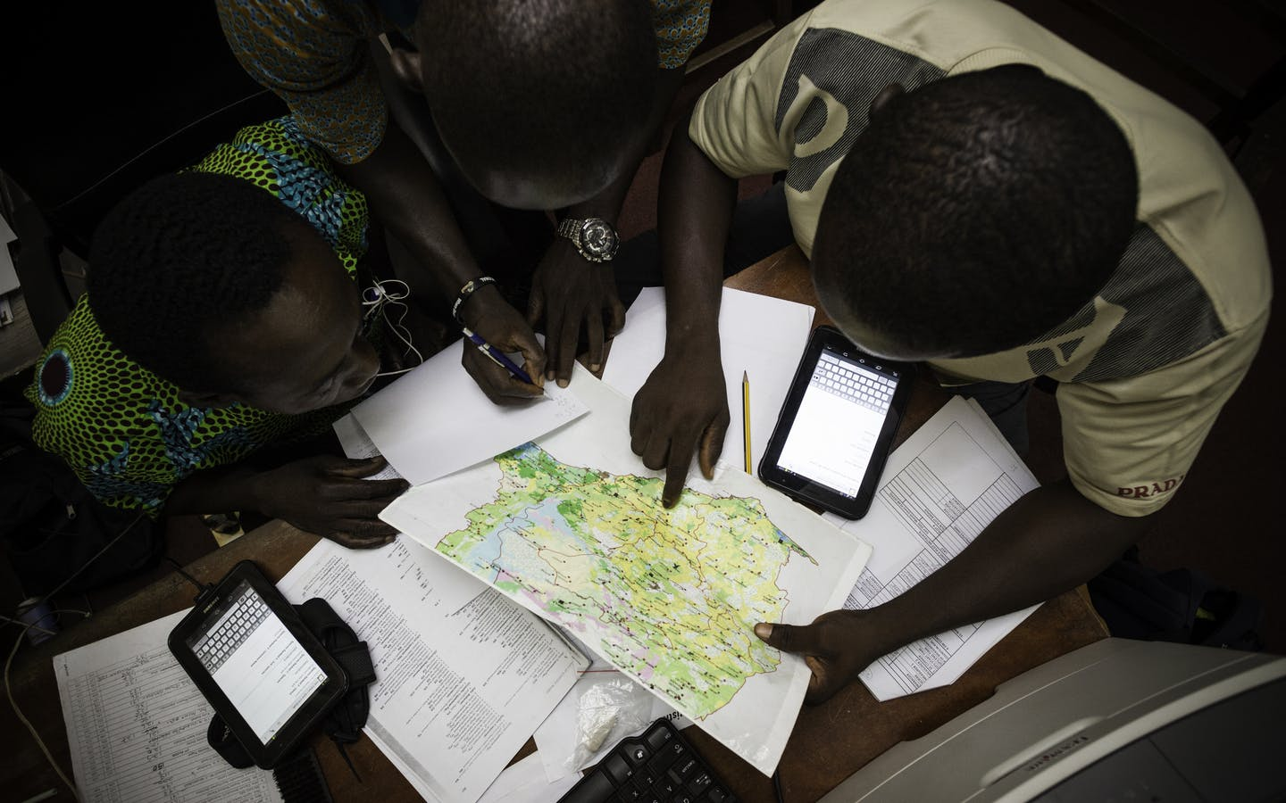 Three men looking at a map of Ghana.