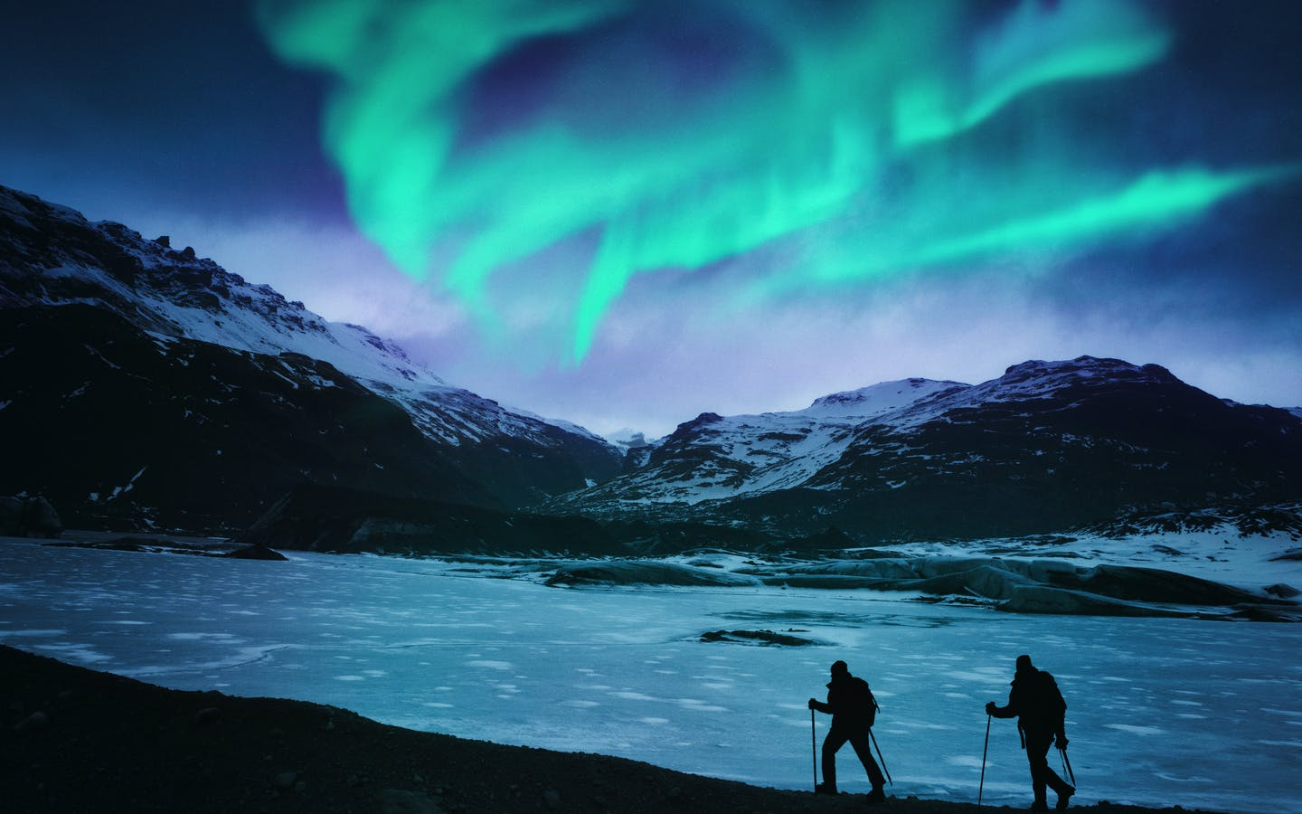 Hikers under the northern lights in Iceland.