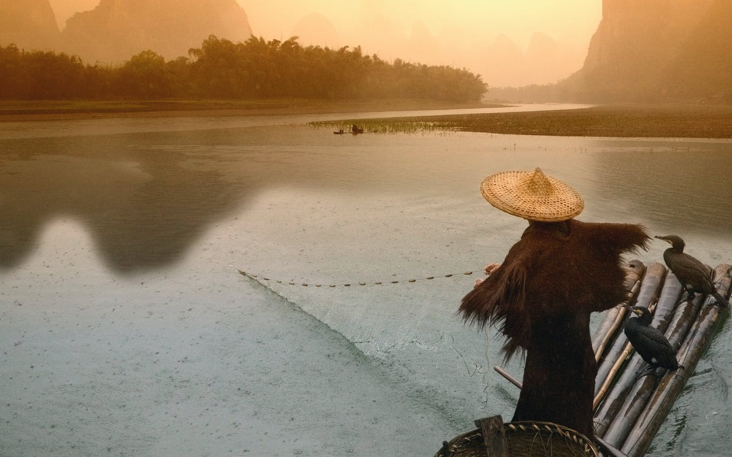 Fisherman casting net from bamboo raft at dawn