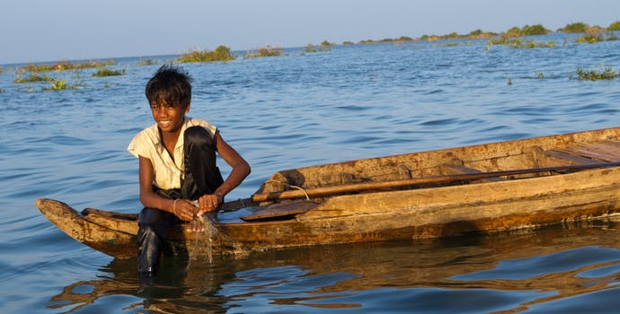 Young boy fishing in Tonle Sap at sunset.