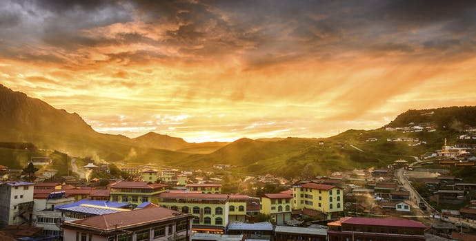 Skyline of a small rural town with rolling hills in Tibet during sunset.