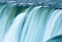 Blue green water racing over the edge of Niagara Falls, Canada