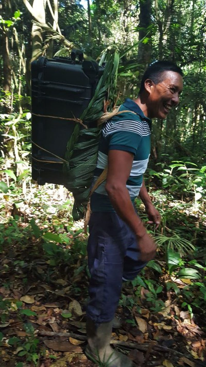 Local guide models a backpack made of palm fronds to carry camera gear in southern Suriname.