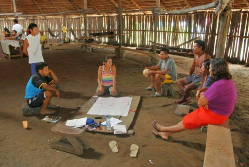 Researcher (kneeling in the center) conducting participatory surveys in Comejahu indigenous village in the Colombian Amazon.